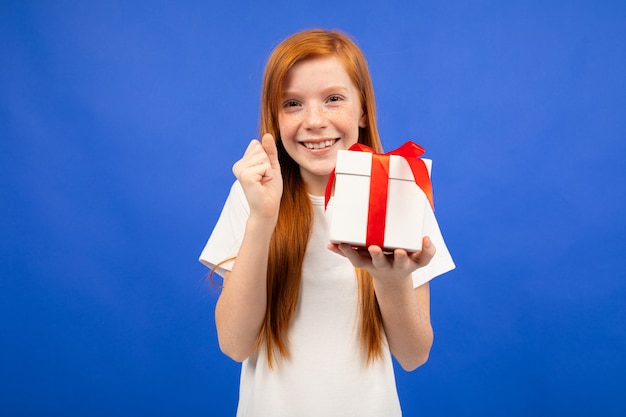 De gelukkige blije tiener met rood haar ontving een verjaardagsgeschenkblauw