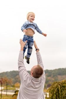 De gelukkige blije vader die pret heeft werpt in het luchtkind. familie, reizen, vakantie, vaderdag concept.