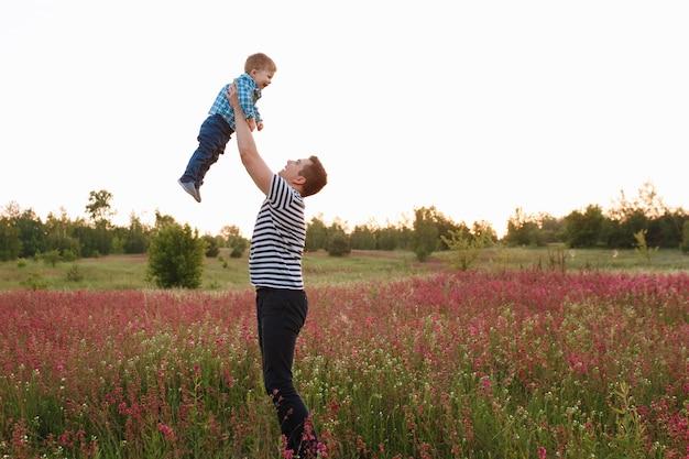 De gelukkige blije vader die pret heeft werpt omhoog in het luchtkind. zonlicht op de zonsondergang
