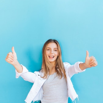 De gelukkige blonde jonge vrouw die duim toont ondertekent omhoog tegen blauwe achtergrond