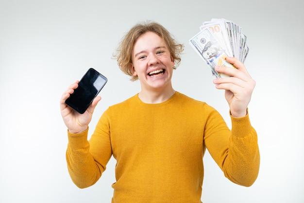 De gelukkige blonde kerel houdt zijn salaris en smartphone met een model op een wit