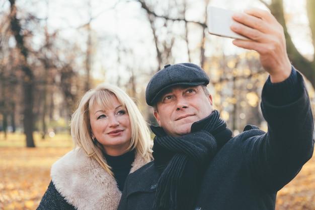 De gelukkige blonde rijpe vrouw en het mooie brunette op middelbare leeftijd nemen selfie op mobiele telefoon.