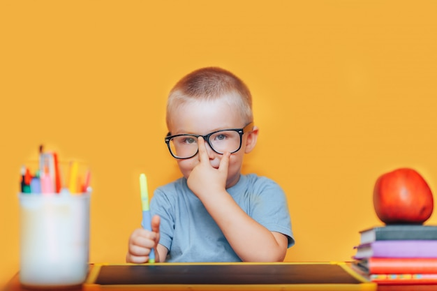 De gelukkige blonde slimme jongen zit bij een bureau in glazen en het glimlachen
