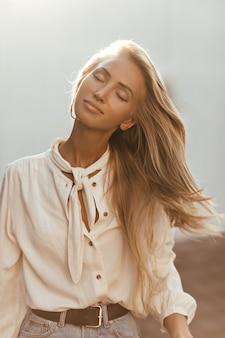De gelukkige blonde vrouw in witte blouse en denimrok speelt haar