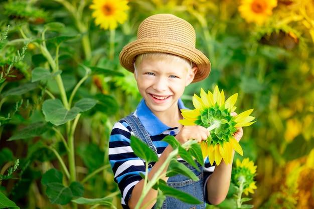 De gelukkige blonde zitting van de babyjongen in een veld met zonnebloemen in de zomer