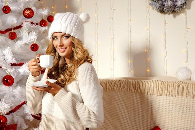 De gelukkige blondevrouw met kerstmis stelt voor