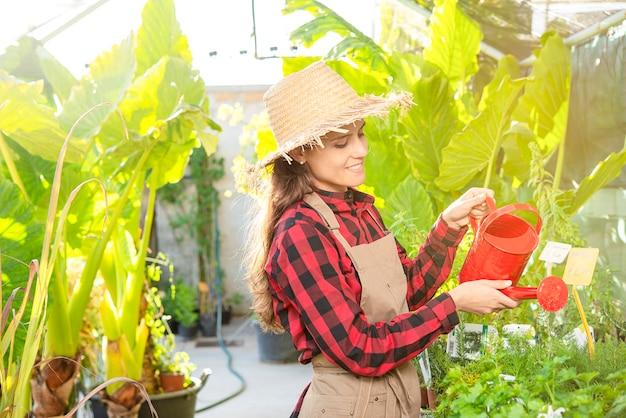 De gelukkige boer die de planten water geeft met kan in een groen bedrijfsconcept van de planten- en bloemenwinkel