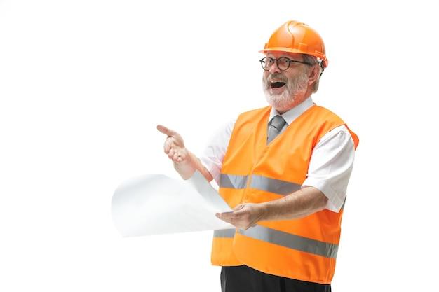 De gelukkige bouwer in een bouwvest en een oranje helm die bij studio glimlachen