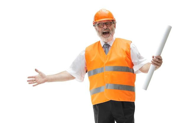 De gelukkige bouwer in een bouwvest en een oranje helm die lacht in de studio. veiligheidsspecialist, ingenieur, industrie, architectuur, manager, beroep, zakenman, baanconcept