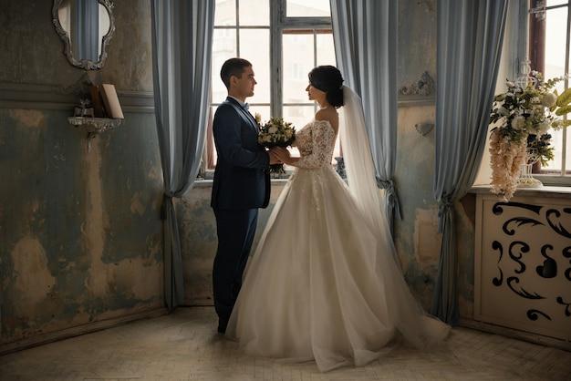 De gelukkige bruid en bruidegom zijn één-op-één blikken en houden een boeket. pasgetrouwden staan in een vintage interieur voor het raam.