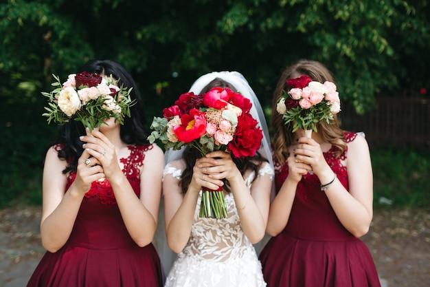 De gelukkige bruid en haar vrienden houden mooie bloemen