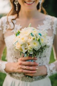 De gelukkige bruid houdt een huwelijksboeket van witte rozen
