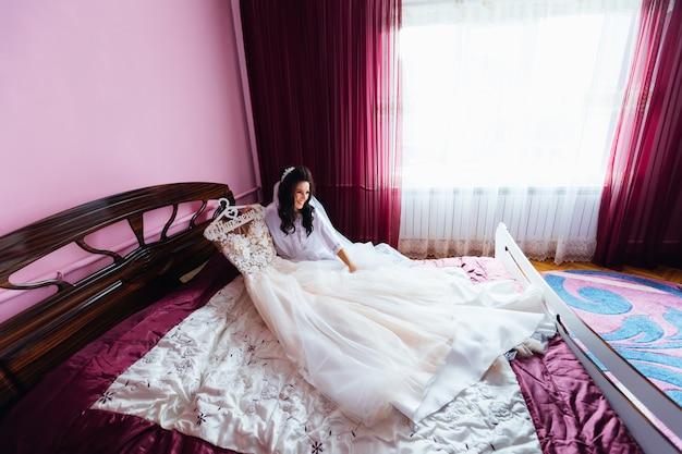 De gelukkige bruid in badjas zit op bed in slaapkamer en houdt huwelijk
