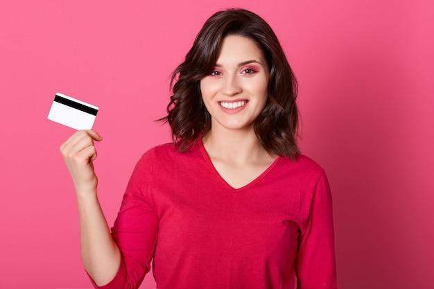 De gelukkige creditcard van de vrouwenholding in handen, bekijkend camera met brede glimlach, hebbend veel geld om online te winkelen, dragend rood toevallig overhemd, heeft donker haar.
