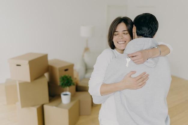 De gelukkige donkerbruine glimlachende vrouw omhelst met liefde haar echtgenoot, houdt sleutels