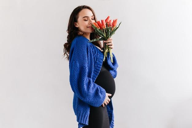 De gelukkige donkerbruine vrouw in blauw vest en zwarte kleding ruikt tulpen. charmante zwangere dame houdt boeket bloemen op geïsoleerd.