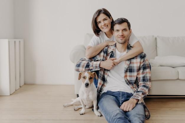 De gelukkige donkerbruine vrouw omhelst echtgenoot met liefde, die in goed humeur is, glimlacht positief. man, vrouw en hond poseren samen in de woonkamer van een nieuwe woning, genieten van comfort. verliefde paar binnen