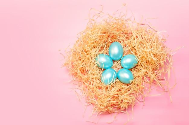 De gelukkige eenvoudige achtergrond van pasen, gekleurde parel blauwe eieren in hooinest over heldere roze kleur