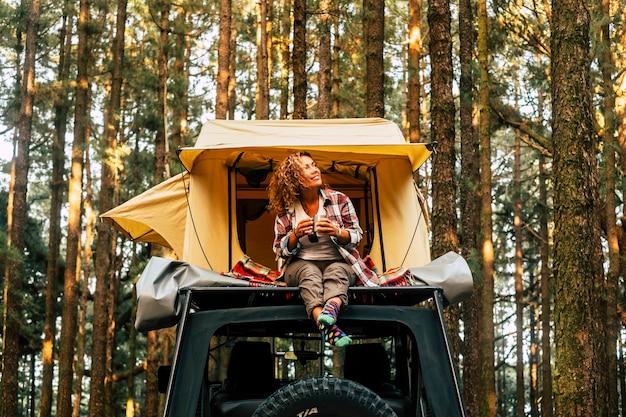 De gelukkige eenzame volwassen vrouw gaat op de auto van de daktent zitten