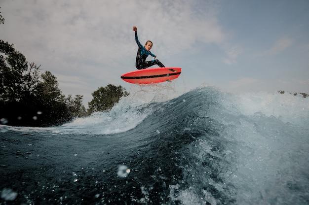 De gelukkige emotionele jongen kleedde zich in het zwarte en blauwe zwempak surfen die omhoog op oranje raad springen