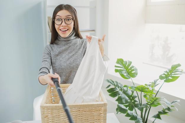 De gelukkige en aardige vrouw houdt witte kleren in haar hand en neemt er foto's van