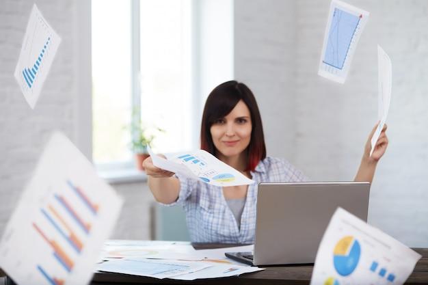 De gelukkige en glimlachende vrouwelijke werknemer werpt documenten in bureau met rond dalende documenten. werk op tijd afmaken.