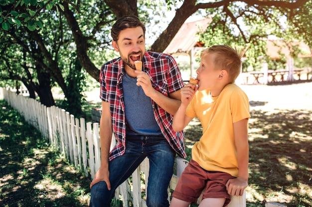 De gelukkige en opgewekte ouder bekijkt zijn zoon en eet roomijs