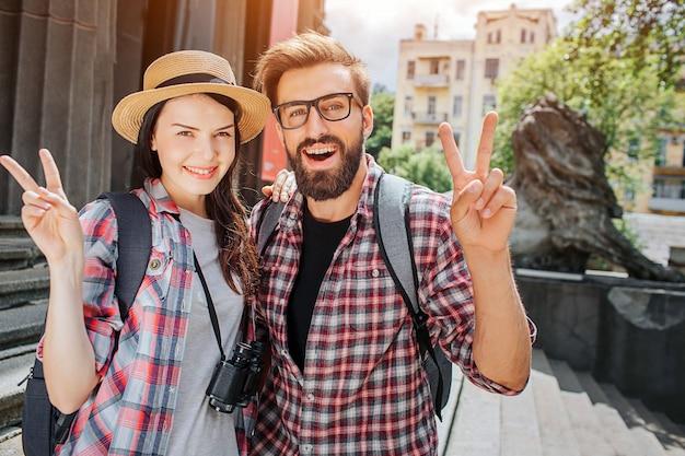 De gelukkige en positieve reizigers staan buiten dicht bij stappen en stellen op camera. ze tonen stuk symbool. vrouw heeft verrekijker. ze zien er mooi en mooi uit.