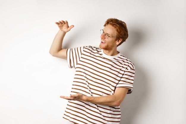 De gelukkige en tevreden blanke roodharige man introduceert iets groots, toont een groot product en glimlacht tevreden, witte achtergrond.