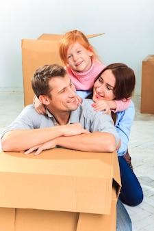 De gelukkige familie bij reparatie en verhuizing op een achtergrond van dozen
