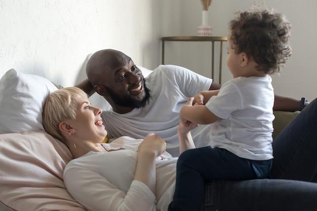 De gelukkige familie die thuis rust, een multicultureel gezin