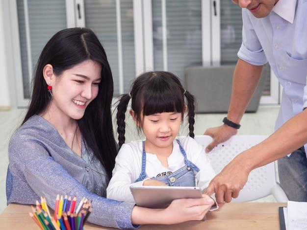 De gelukkige familie doet samen activiteiten, zijn de kinderen laptop, familieconcept gebruiken
