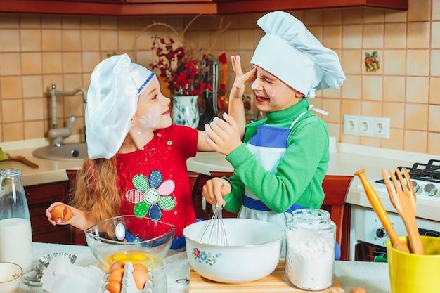 De gelukkige familie grappige jonge geitjes bereiden deeg voor, bakken koekjes in keuken