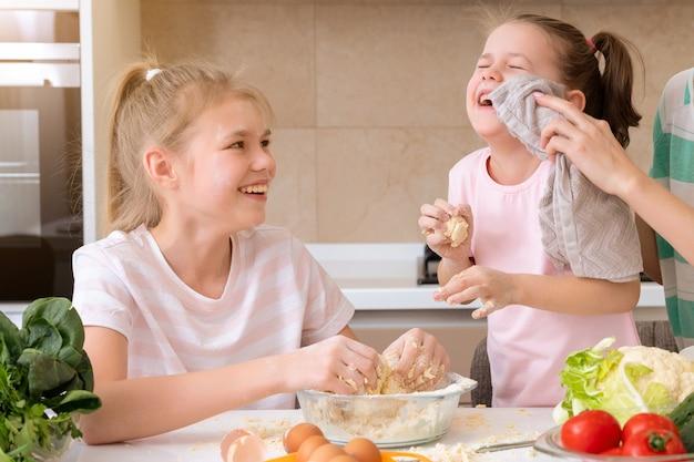 De gelukkige familie grappige jonge geitjes bereiden het deeg voor, bakken koekjes in de keuken. zusters plezier samen lachen