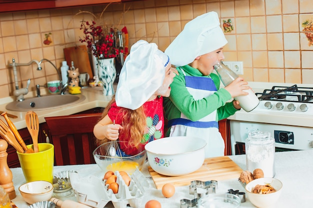 De gelukkige familie grappige jonge geitjes bereiden het deeg voor, bakken koekjes in de keuken