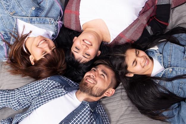 De gelukkige familie ligt van bovenaf op de plaid