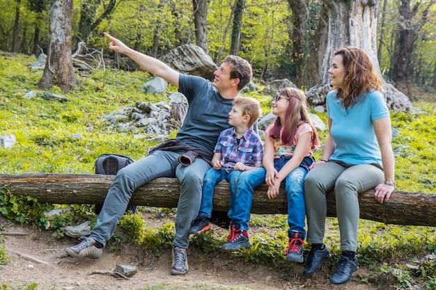 De gelukkige familie zit op de boomstam van een boom in een bos