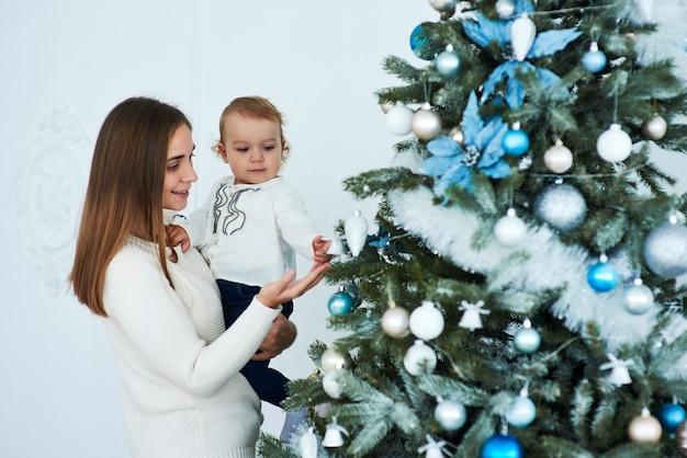 De gelukkige familiemoeder en de baby verfraaien kerstboom