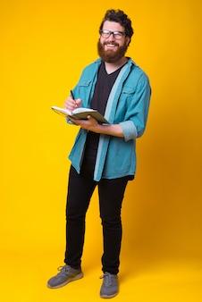 De gelukkige gebaarde hipstermens glimlacht bij de camera terwijl het schrijven in zijn dagboek