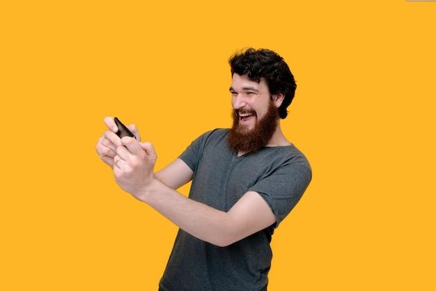 De gelukkige gebaarde kerel speelt met smartphone op geïsoleerde gele muur