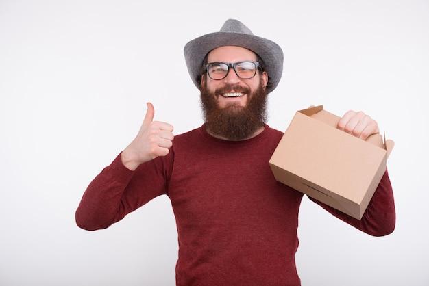 De gelukkige gebaarde mens glimlacht bij de camera, toont duim of houdt als gebaar een lunchdoos. het is etenstijd.