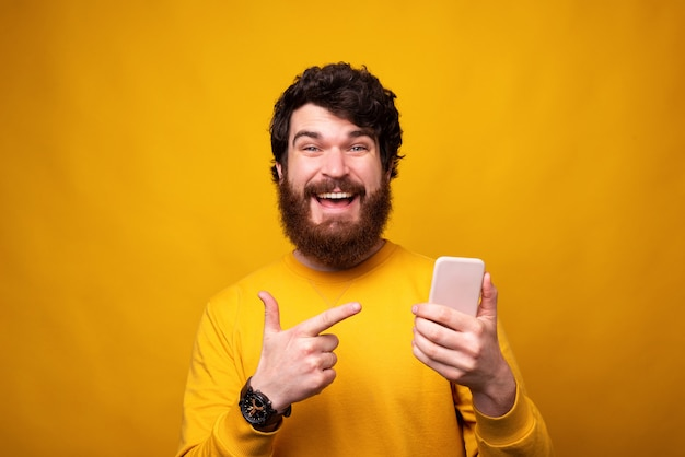 De gelukkige gebaarde mens richt op zijn telefoon die hij op gele achtergrond houdt.