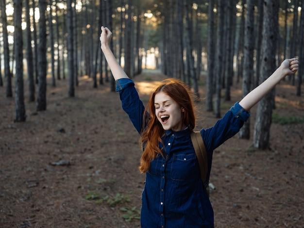 De gelukkige gebaren van de vrouwenwandelaar met zijn handen op aard in de emoties van de dennenbosvreugde