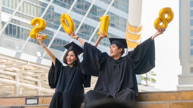 De gelukkige gediplomeerde tienermensen zitten met de graduatietoga's in felicitatieceremonie met impuls 2018.
