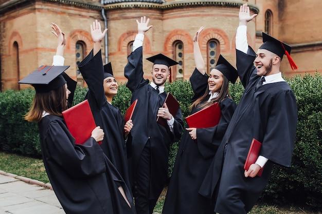 De gelukkige gegradueerde toont diploma's bij ceremonie buiten universiteit