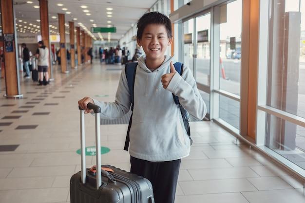 De gelukkige gemengde jongen die van de ras aziatische tween duim opgeven en zijn koffer houden bij de luchthaven