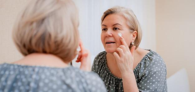 De gelukkige gezonde rijpe vrouw bij spiegel past anti verouderende bevochtigende kosmetische room op gezicht toe, die de zorg en de schoonheid van de dame zachte schone huid op middelbare leeftijd glimlachen