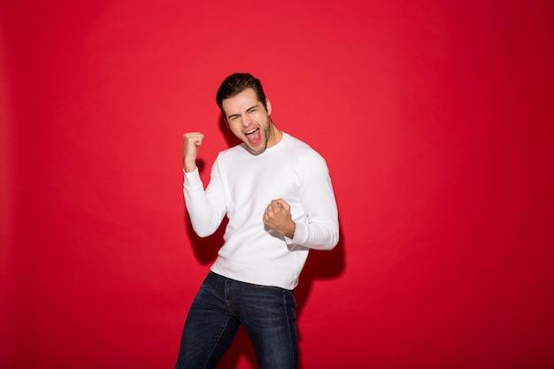De gelukkige gillende mens in sweater verheugt zich en kijkend