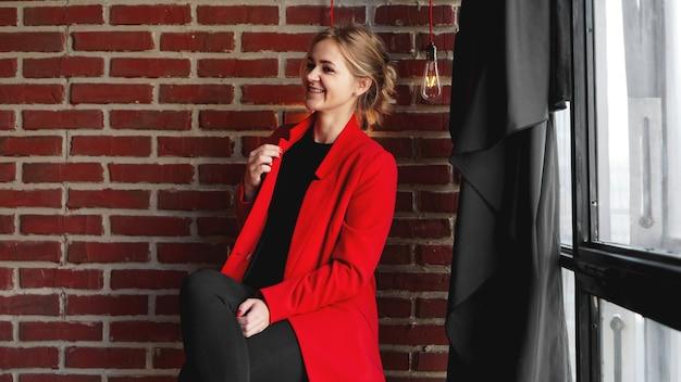 De gelukkige glimlach van de onderneemster draagt rood jasje - bedrijfsvrouw over bureaubakstenen muur