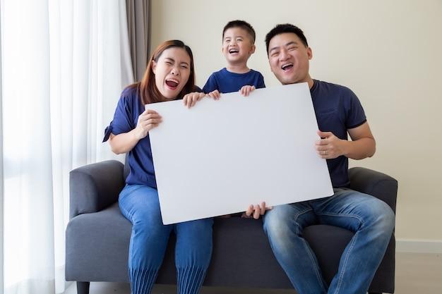 De gelukkige glimlachende aziatische lege grote witte affiche van de familieholding en zitting op bank in woonkamer, wauw en verrast concept